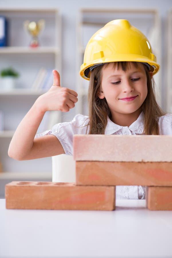 Het jonge meisjesgebouw met bouwbakstenen stock fotografie