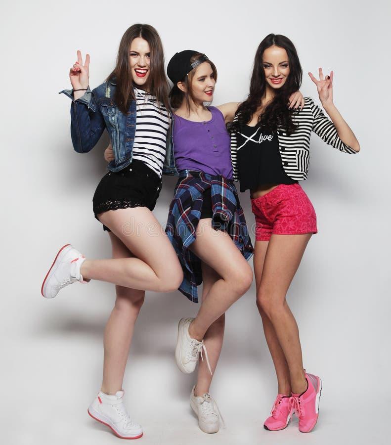 Het jonge meisjesvrienden dansen van vreugde in volledige lengte stock foto