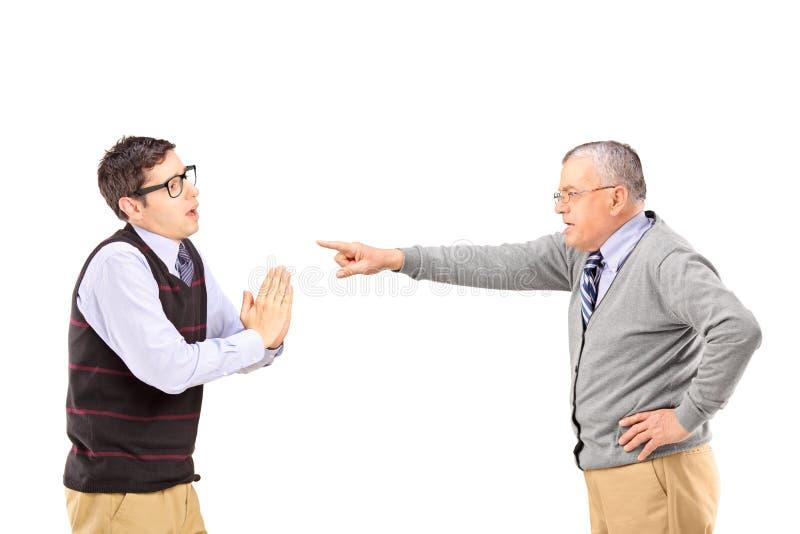 Het jonge mens bedelen en het boze rijpe mens gesturing met vinger stock foto's