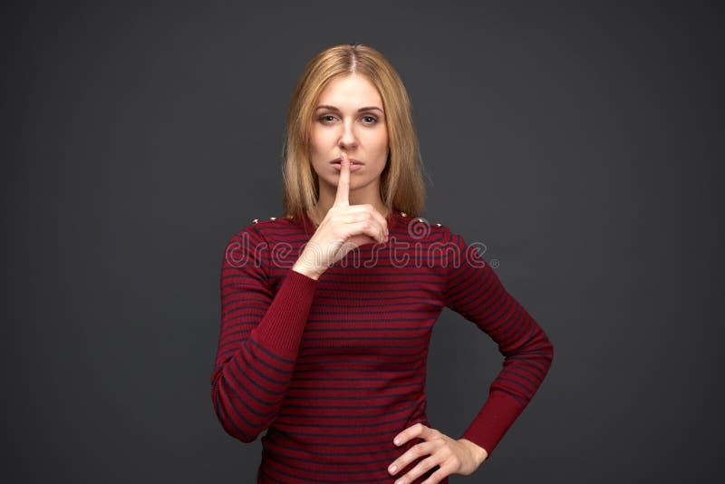 Het jonge modieuze meisje met ernstige uitdrukking toont voorzichtig teken om lawaai niet te maken en geheim iedereen niet te ver stock afbeeldingen