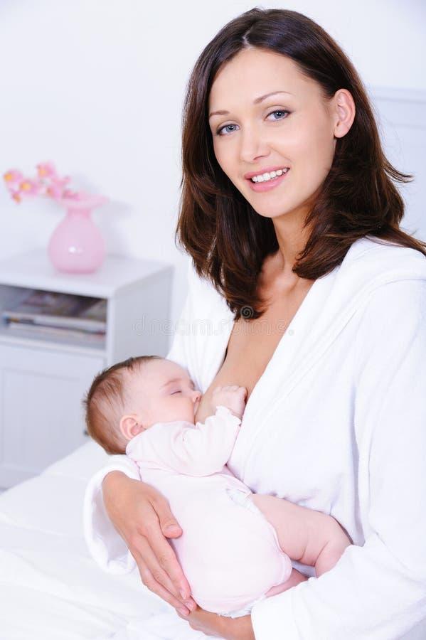 Het jonge moeder brestfeeding voor baby stock afbeelding