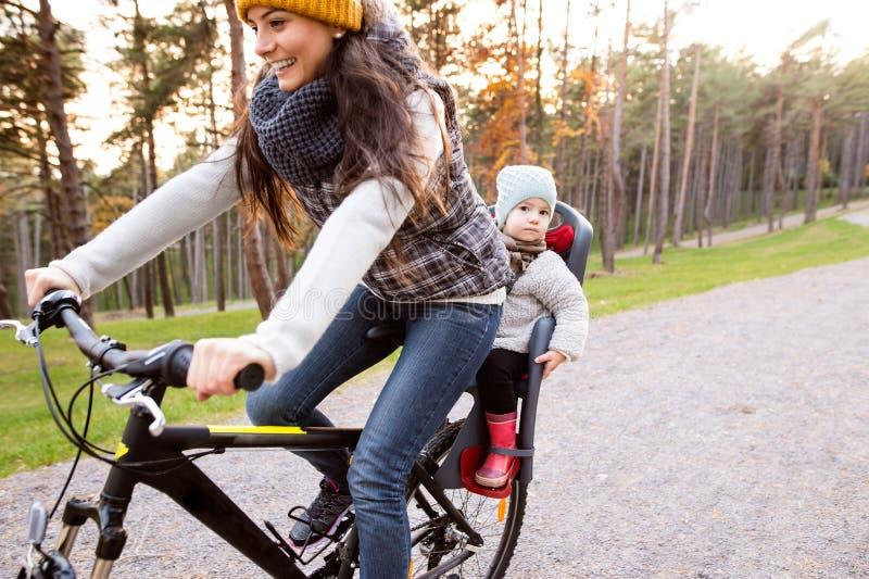 Het jonge moeder en dochter cirkelen in de herfstpark stock fotografie