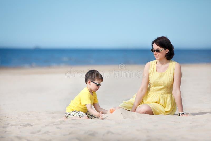 Het jonge moeder en zoons spelen op zandstrand stock afbeeldingen
