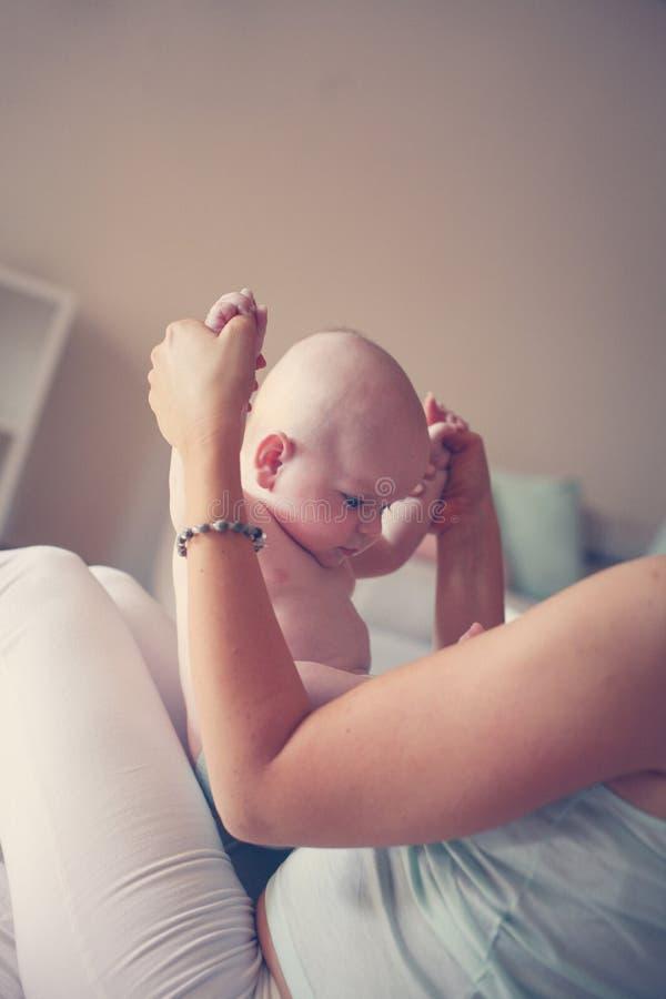 Het jonge moeder spelen met haar babyjongen in bed stock afbeelding