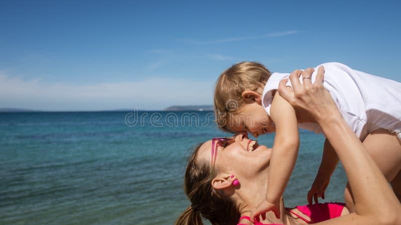 Het jonge moeder spelen met haar dochter door het overzees stock foto