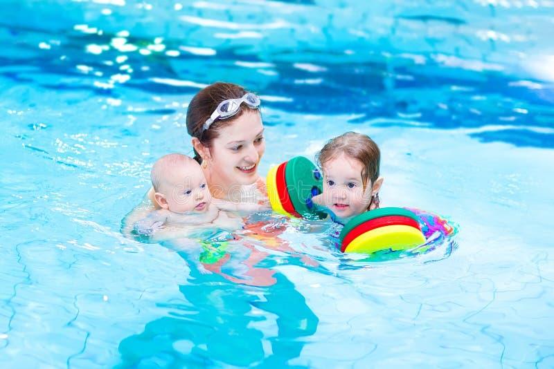 Het jonge moeder spelen met jonge geitjes in zwembad stock afbeelding