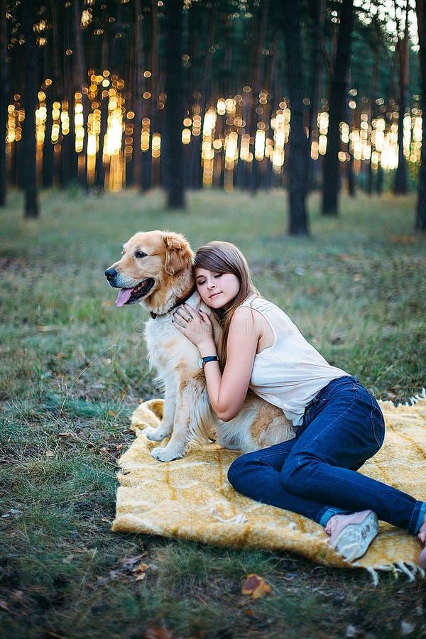 Het jonge mooi en het glimlachen meisje spelen met een hond royalty-vrije stock afbeelding