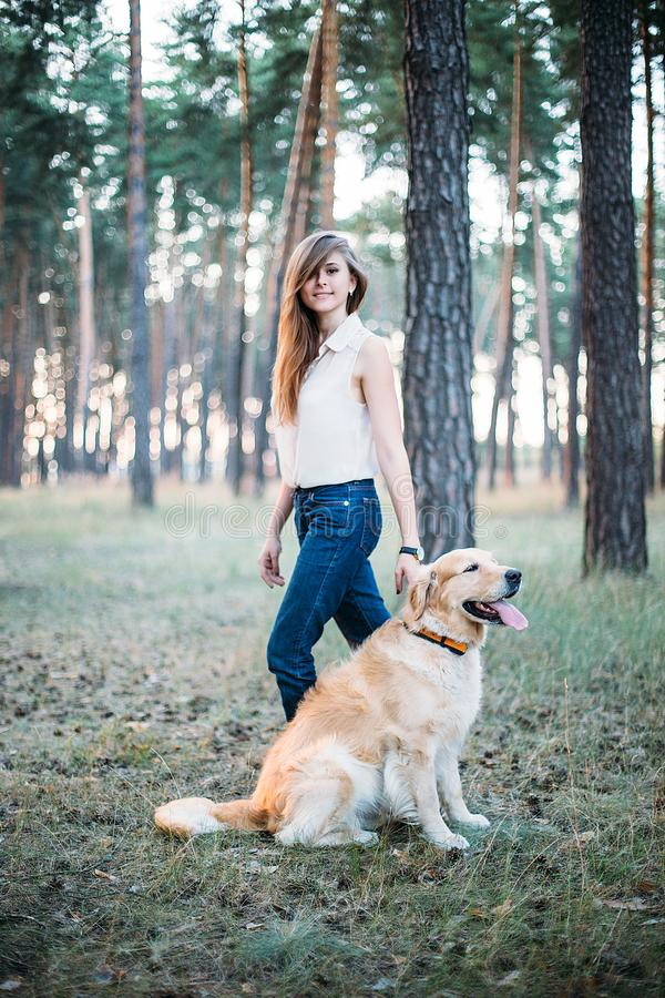 Het jonge mooi en het glimlachen meisje spelen met een hond stock foto's