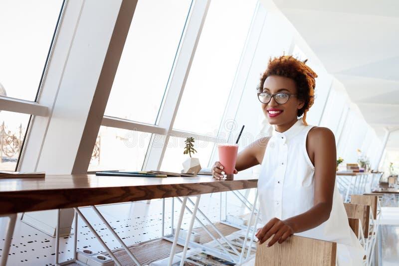 Het jonge mooie Afrikaanse meisje het drinken smoothie het glimlachen rusten in koffie royalty-vrije stock fotografie