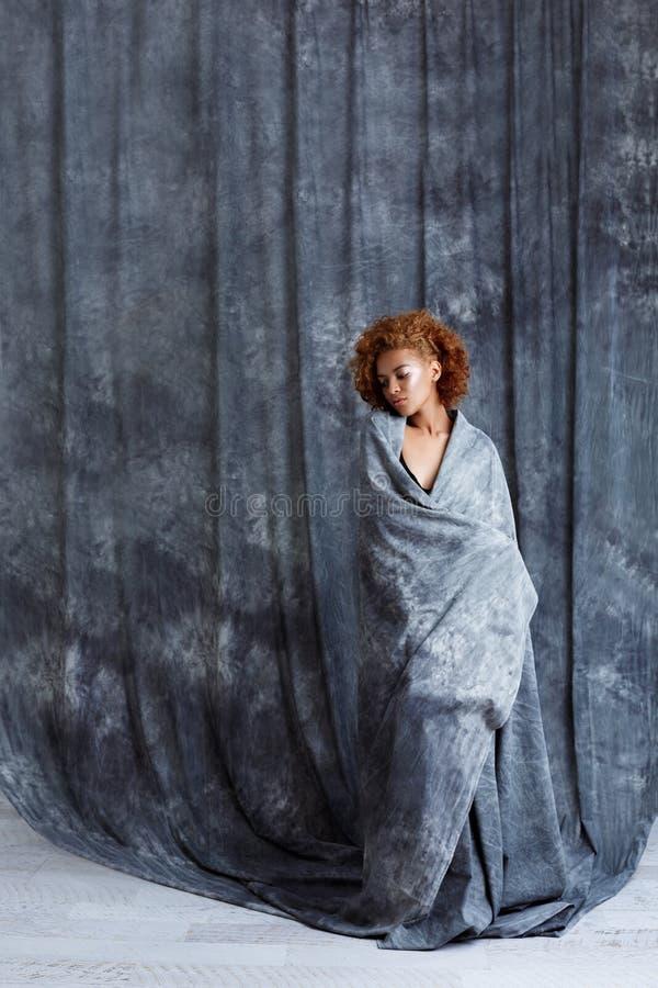 Het jonge mooie Afrikaanse meisje stellen, die omhoog in grijze doek verpakken stock foto