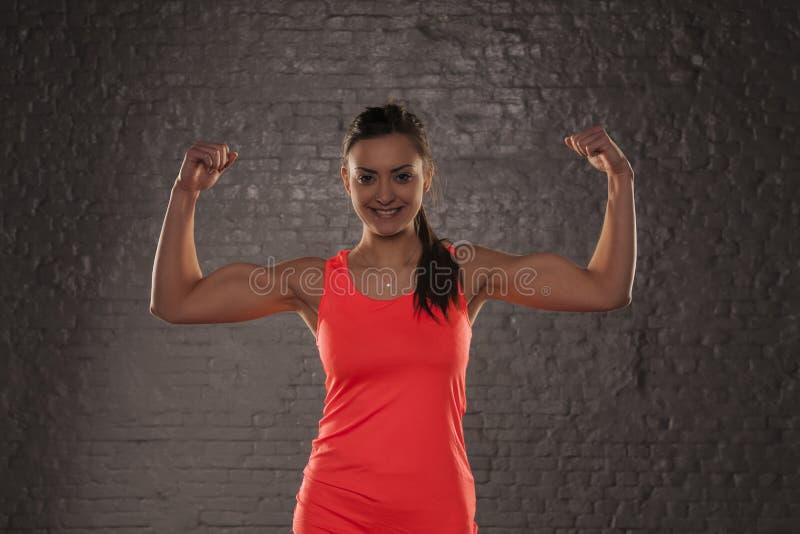 Het jonge mooie atletische meisje toont haar bicepsen royalty-vrije stock afbeeldingen