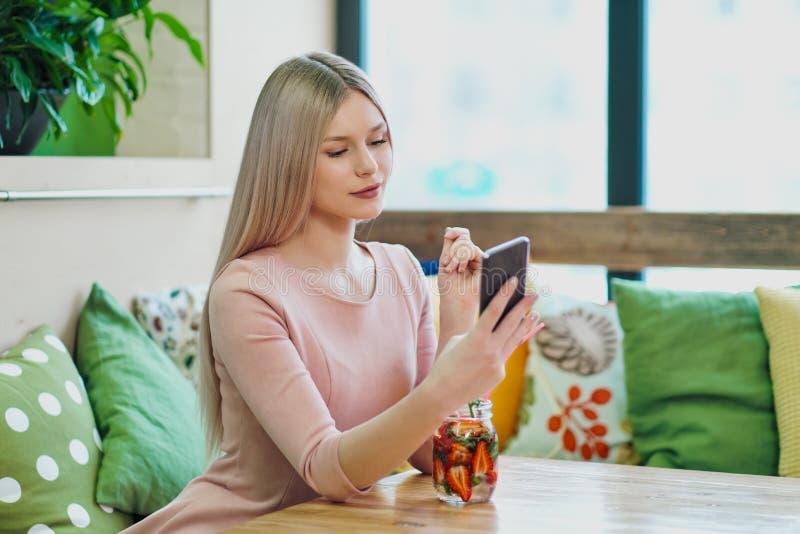 Het jonge mooie blondemeisje in een roze kleding zit bij een koffielijst, drinkt limonade van een glaskruik royalty-vrije stock afbeelding