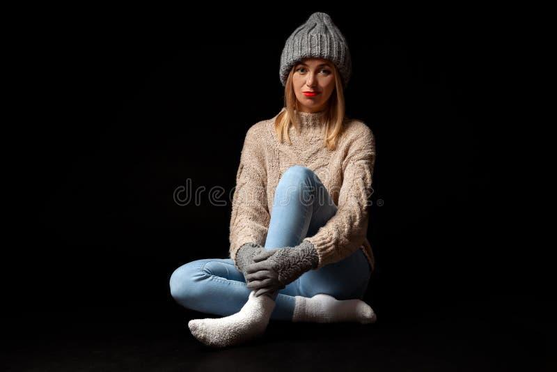Het jonge mooie blondemeisje in gebreide handschoenen en de hoed in grijs, jeans, beige sweater zitten op de vloer met gekruiste  royalty-vrije stock afbeeldingen