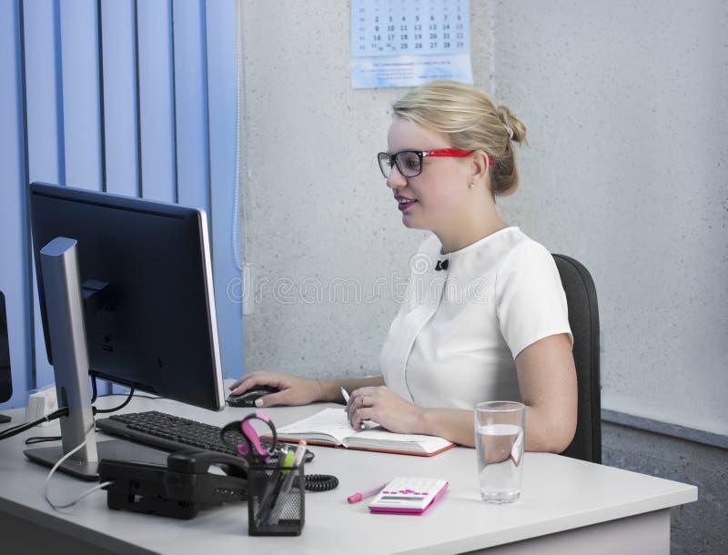 Het jonge mooie blondemeisje werkt in het bureauclose-up stock fotografie