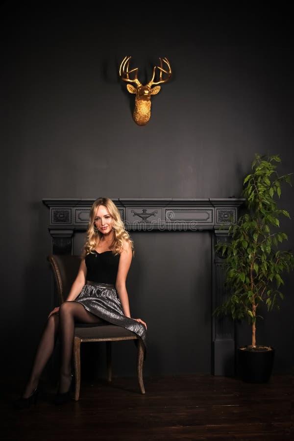 Het jonge mooie blondemeisje zit op de stoel in dicht het gelijk maken van glanzende kleding op de grijze muurachtergrond in de f royalty-vrije stock foto