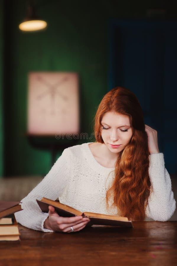 Het jonge mooie boek van de de vrouwenlezing van de roodharigestudent in universitaire bibliotheek royalty-vrije stock fotografie