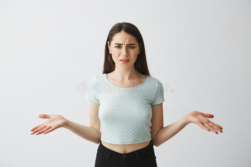 Het jonge mooie donkerbruine meisje die camera bekijken die suspiciously deelt over witte achtergrond uit uitspreiden stock afbeeldingen