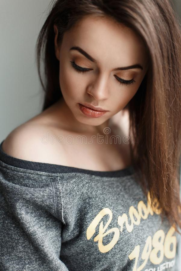 Het jonge mooie donkerbruine meisje in grijs jasje kijkt neer stock afbeelding