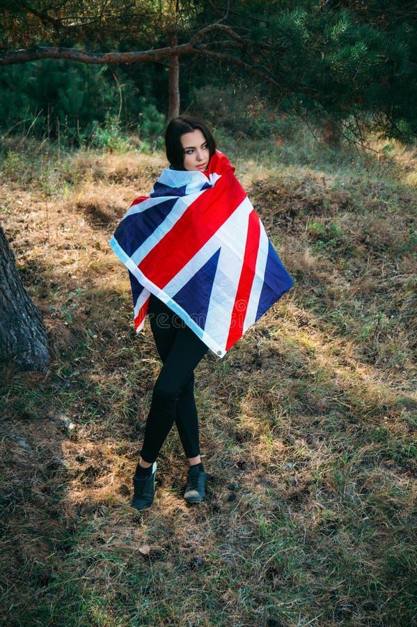 Het jonge mooie donkerbruine meisje stellen met een Britse vlag in de herfstpark royalty-vrije stock afbeelding