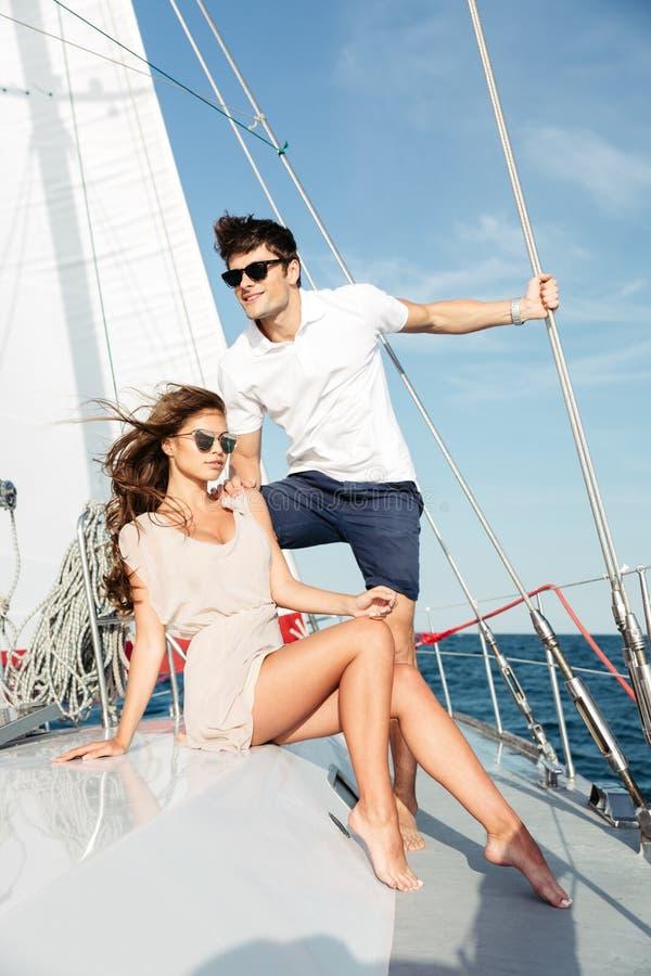 Het jonge mooie echtpaar ontspannen op het jacht stock foto's