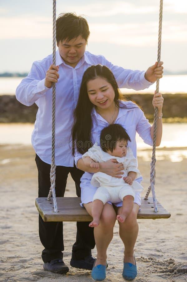 Het jonge mooie en gelukkige Aziatische Chinese paar met babymeisje die van romantische de zomervakantie genieten haalt bij stran stock foto's