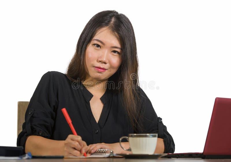 Het jonge mooie en gelukkige succesvolle Aziatische Chinese bedrijfsvrouw werken ontspande bij het bureau van de bureaucomputer g stock foto's
