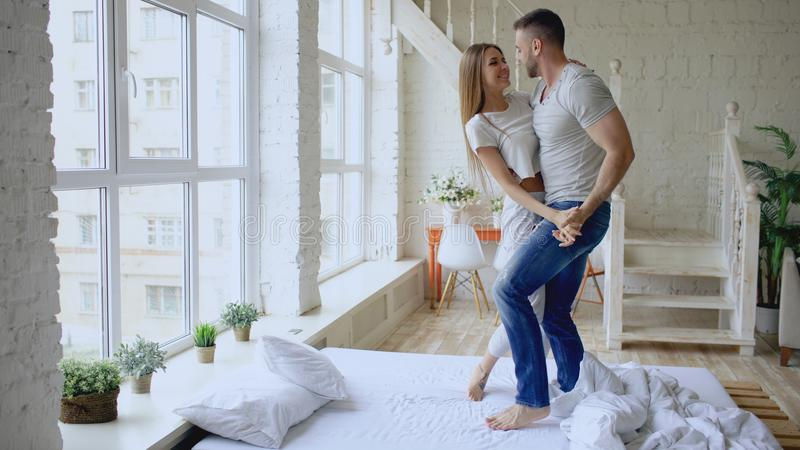 Het jonge mooie en houdende van paar die rocknroll danst thuis op bed in de ochtend dansen stock afbeelding