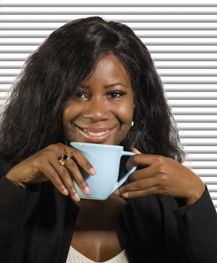 Het jonge mooie en succesvolle zwarte afro Amerikaanse onderneemster het drinken koffie glimlachen zeker en ontspannen op bureauz stock afbeeldingen