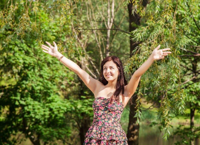 Het jonge mooie glimlachende meisje houdt haar handen aan de hemel stand royalty-vrije stock afbeeldingen