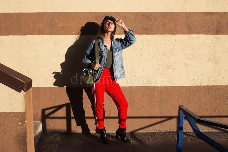 Het jonge mooie hipster vrolijke meisje stellen op de straat bij zonnige dag, die alleen pret, modieuze kleren en glazen hebben stock afbeeldingen