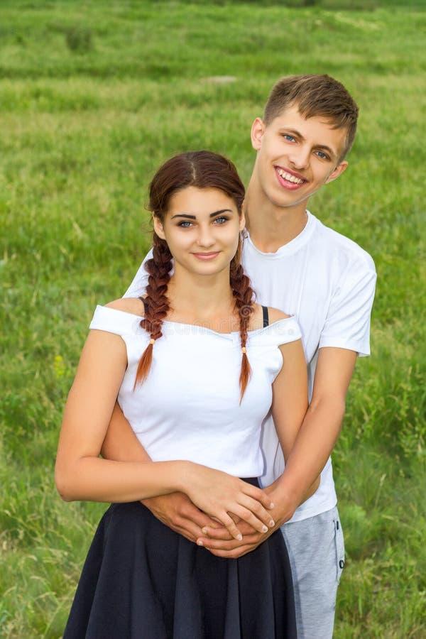 Het jonge mooie leuke paarmeisje en de kerel bevinden zich wapen in wapen op een achtergrond van aard, het concept de verhouding stock afbeeldingen