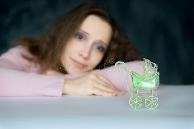 Het jonge mooie meisje bekijkt hopelijk een kinderwagenstuk speelgoed De wandelwagen in de voorgrond, een vrouw in het vage ondui royalty-vrije stock foto's