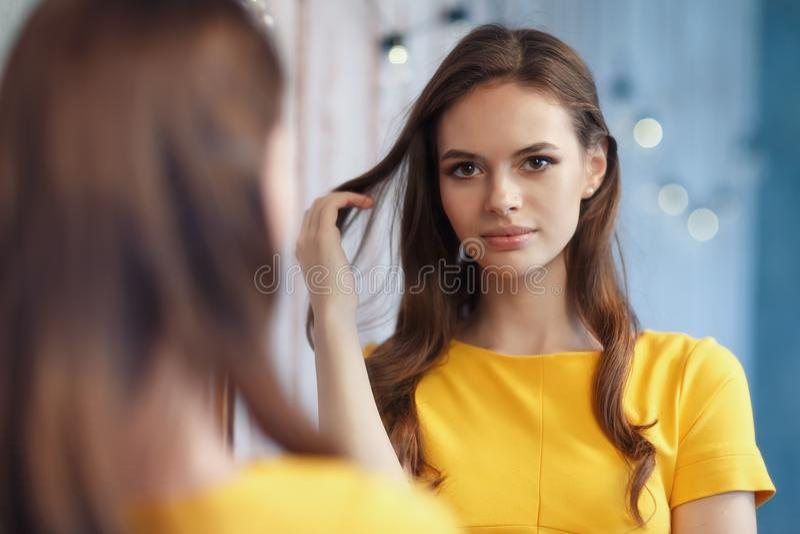 Het jonge mooie meisje bekijkt zich in de spiegel stock afbeeldingen