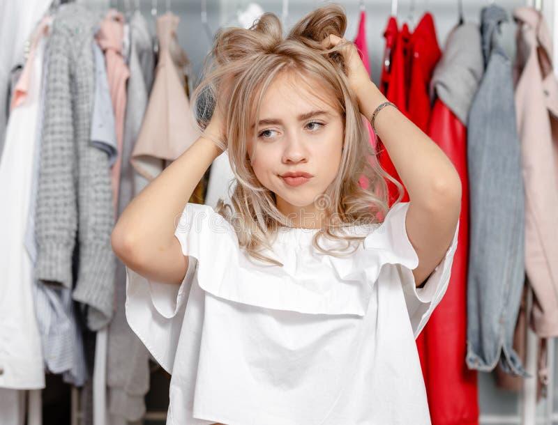 Het jonge mooie meisje blogger bevindt zich met een nadenkende uitdrukking op zijn gezicht op de achtergrond van kleren die op a  stock foto's