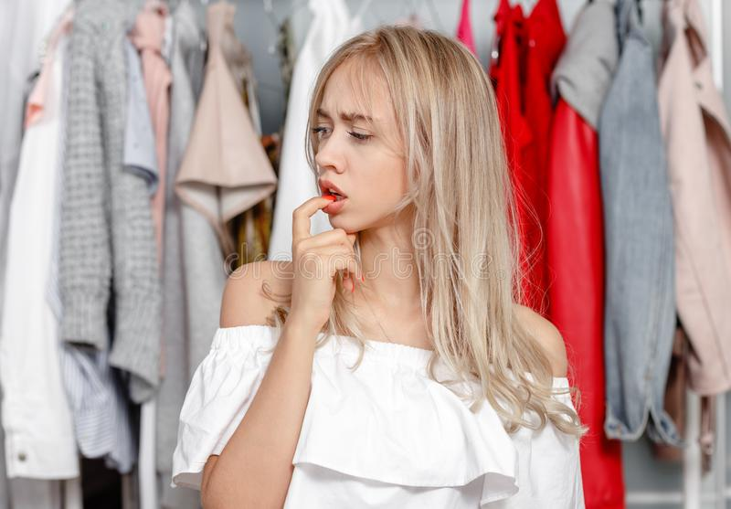 Het jonge mooie meisje blogger bevindt zich met een nadenkende uitdrukking op zijn gezicht op de achtergrond van kleren die op a  stock foto