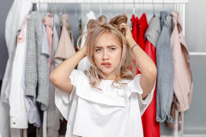 Het jonge mooie meisje blogger bevindt zich met een nadenkende uitdrukking op zijn gezicht op de achtergrond van kleren die op a  royalty-vrije stock fotografie