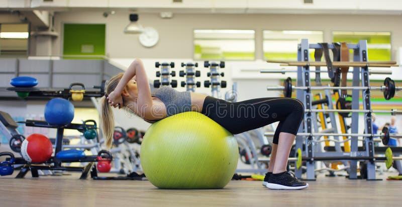 Het jonge mooie meisje in de gymnastiek, slingert de pers met de bal die voor geschiktheid, de spieren van de pers en het achterc royalty-vrije stock afbeelding