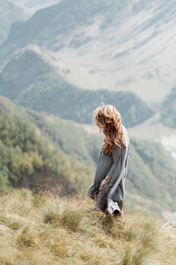 Het jonge mooie meisje in een lange kleding bevindt zich door de klip op de achtergrond van bergen royalty-vrije stock foto