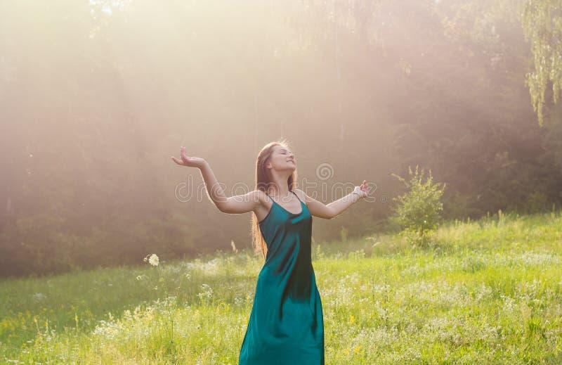 Het jonge mooie meisje geniet van zonlicht, die haar handen omhoog op a opheffen stock foto's