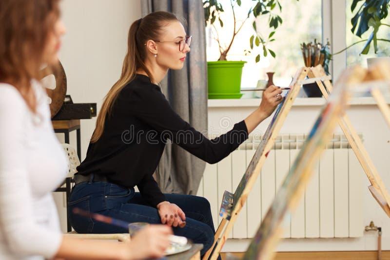 Het jonge mooie meisje in glazen gekleed in zwarte blouse en jeans zit bij de schildersezel en schildert een beeld in de tekening royalty-vrije stock foto