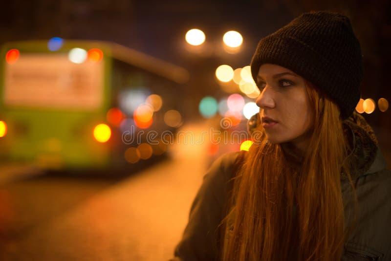 Het jonge mooie meisje haalt een taxi in de stadsstraat bij nacht stock afbeelding