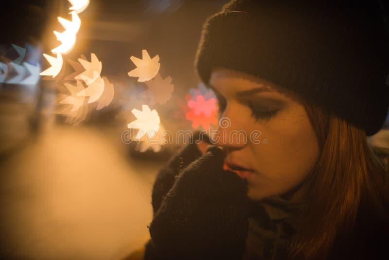 Het jonge mooie meisje haalt een taxi in de stadsstraat bij nacht stock foto's