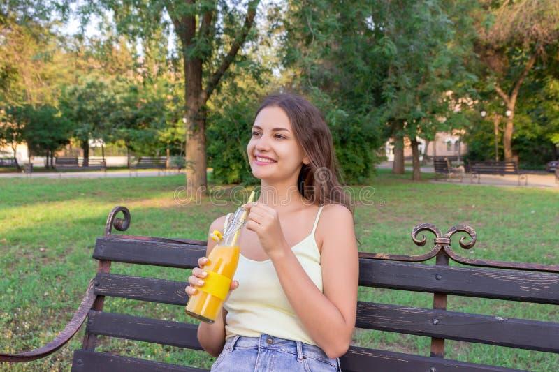 Het jonge mooie meisje heeft rust op de bank in het park en drinkt vers sap van een fles door het stro stock foto