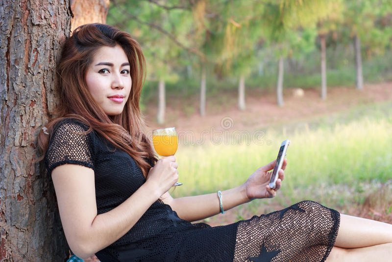 Het jonge mooie meisje het drinken jus d'orange en het Jonge wijfje beweren royalty-vrije stock afbeeldingen
