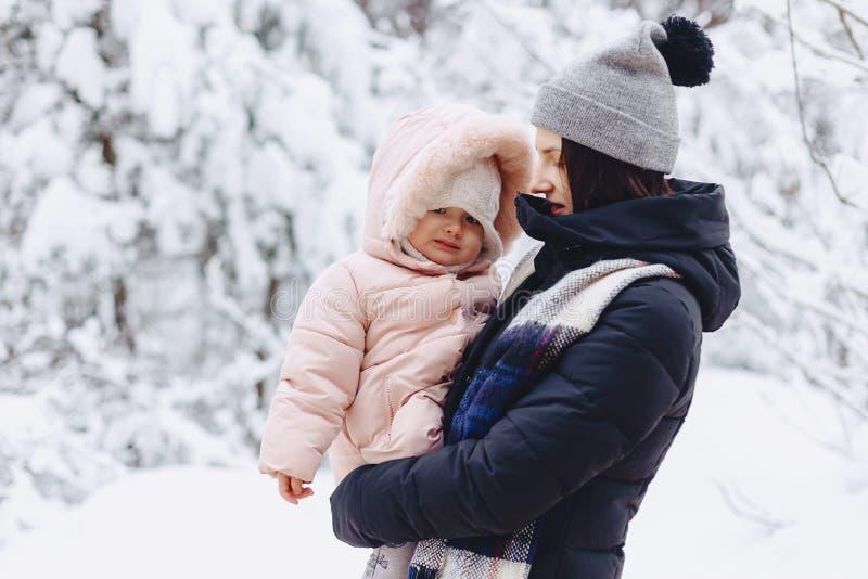 het jonge mooie meisje houdt de kleine baby op haar de winter indient stock foto
