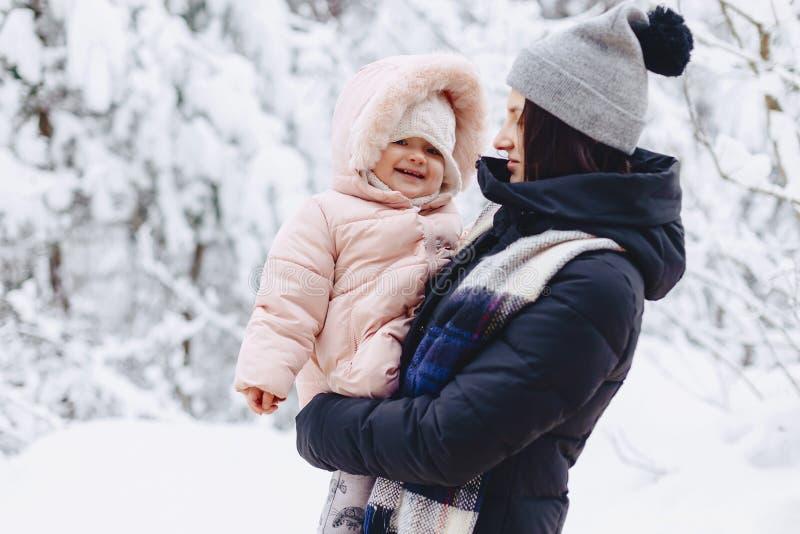 het jonge mooie meisje houdt de kleine baby op haar de winter indient royalty-vrije stock afbeeldingen