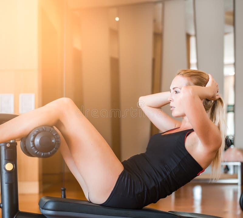 Het jonge mooie meisje in korte sportborrels in fitness in de gymnastiek schudt buikspieren op sportentrainer royalty-vrije stock afbeelding