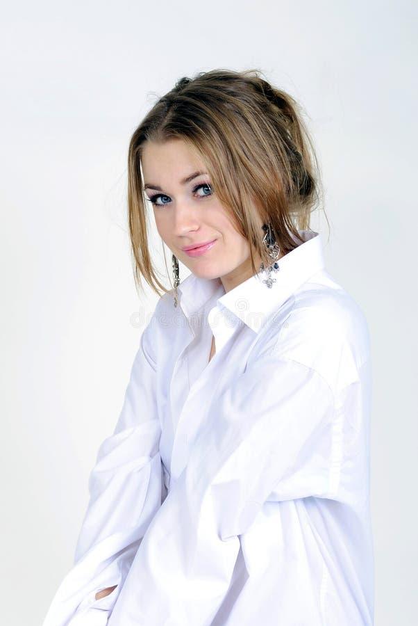 Het jonge mooie meisje ligt in een man overhemd royalty-vrije stock afbeelding