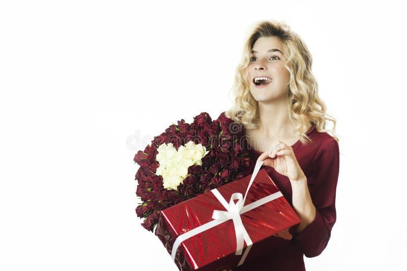 Het jonge mooie meisje met een rode gift met een witte boog en bloemen in haar handen verheugt zich op een geïsoleerde witte acht royalty-vrije stock afbeeldingen