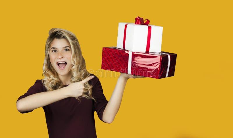 Het jonge mooie meisje met een witte gift met een rode boog en harten in haar handen verheugt zich op een geïsoleerde achtergrond royalty-vrije stock afbeeldingen